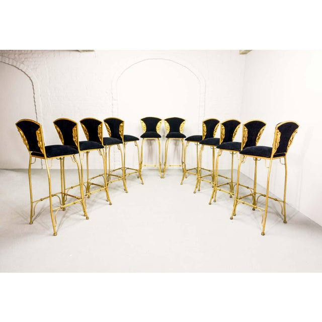 This beautiful set of ten - gilded with gold leaf - 'COBRA' sculptured bar stools and with a rich black fabric upholstered...