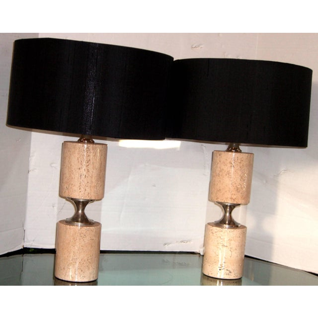 A pair of cylindrical form taupe tone natural stone table lamps. The center is a hourglass shaped nickel. New silk shades...