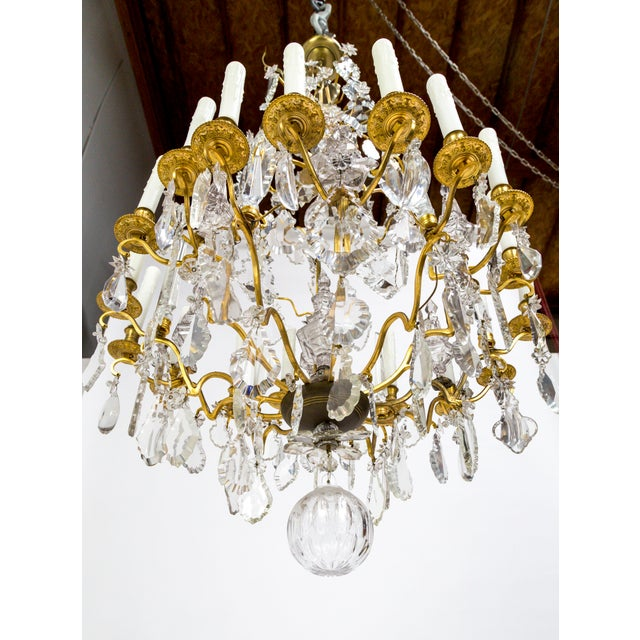 A magnificent, gilt bronze chandelier with 18 undulating arms; decked with spire, star, spear, flower, almond, and...
