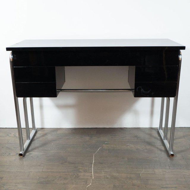 This elegant Art Deco Machine Age desk or vanity in the style of Gilbert Rohde. It features a rectilinear body with a...