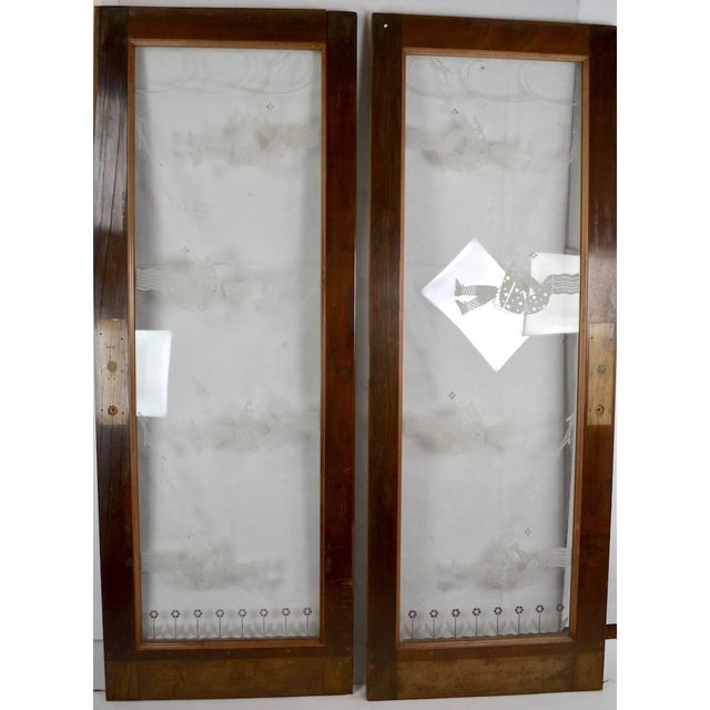 Pair of Art Deco doors, each having a deeply etched centre panel depicting stylized young girls on a swing. The centre...