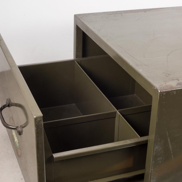 ABOUT An army green industrial factory metal cabinet with original label, brass pull and one segmented drawer. Solidly...