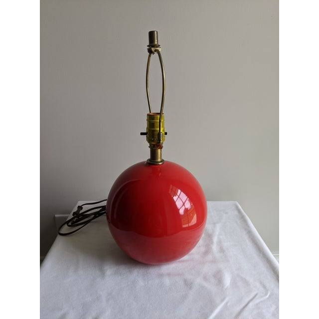 Cute spherical ceramic table lamp with glossy bright red glaze. Brass neck and fittings. Underside with label Mfg. By Mar-...