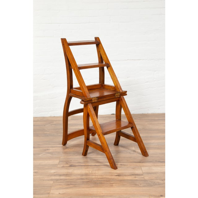 A vintage Indonesian teak wood Dutch Colonial metamorphic ladder chair from the midcentury period. This exquisite and...