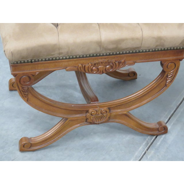 Pair of Regency style carved wood X benches with tufted upholstery and nail head trim.