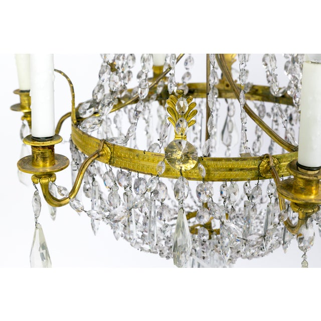 This Regency, tent and bag style, crystal chandelier has lovely brass fleurets, and crystal ropes, swags, and pendants;...