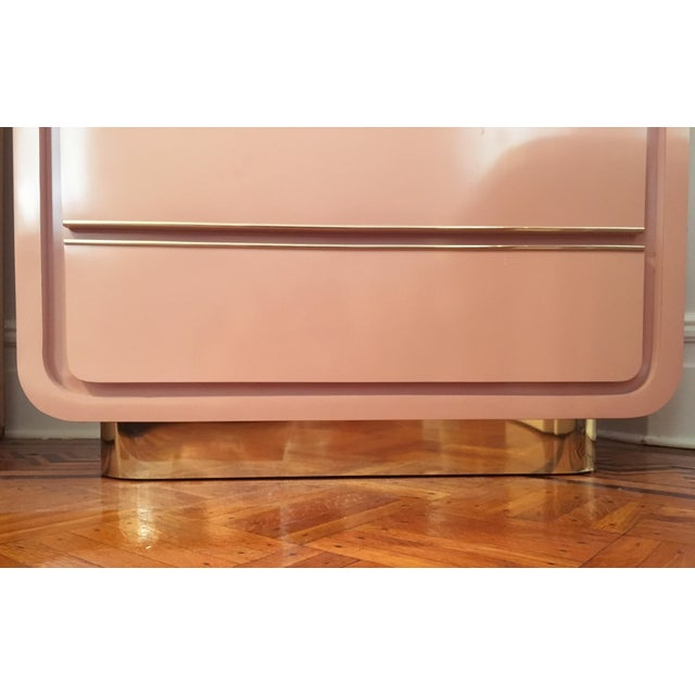 Modern 80s waterfall shape rose pink armoire with gorgeous curved brass trim base. The laminate / formica is glossy,...