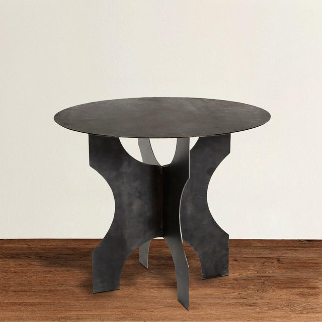 An uber chic modern steel round table with a brutalist attitude, constructed with four legs welded together under a round...