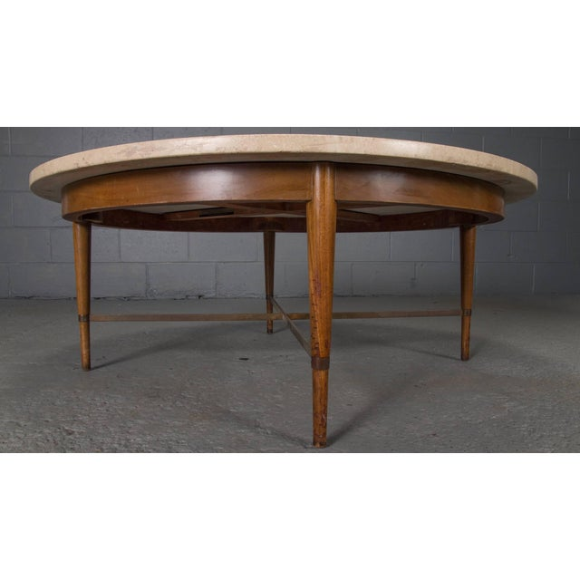 Made of travertine, walnut, and brass, this coffee or cocktail table was designed by Paul McCobb for the Conoisseur...