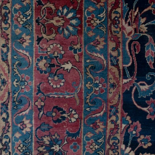 A 19th century Persian Yadz carpet with tree of life pattern on an indigo background, surrounded by a contrasting floral...