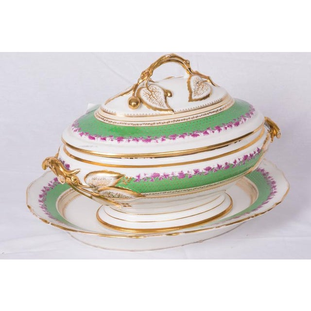 This is an Old Paris oval porcelain lidded tureen decorated with apple green bands and aubergine florets. The lid is...