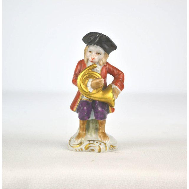 A charming porcelain monkey musician playing the French Horn. The hand painted details are so finite and detailed....