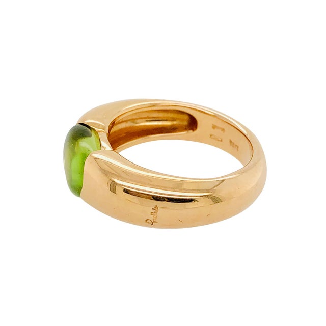 """A fine Italian 18K rose gold ring by Pomellato. The ring is a """"Sassi"""" collection piece with a polished peridot. The ring..."""