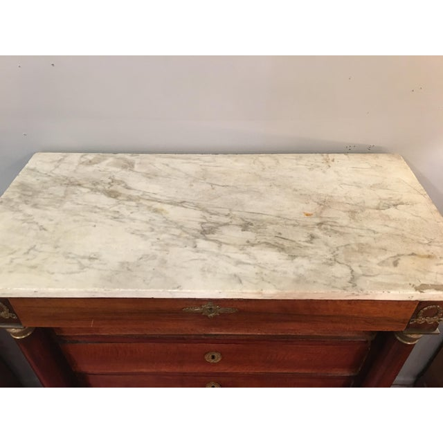 This stately chest of drawers has a marble top and uniquely Empire-style details. Some wear to the wood and marble, as...