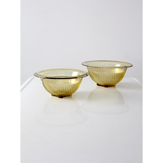 A set of two Depression glass bowls. The ribbed golden yellow bowls feature a rolled edge room and square pedestal bases....