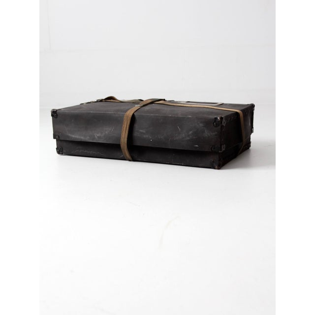 This is a vintage laundry mailing box from the early 20th century. The black fiberboard case features metal corners,...