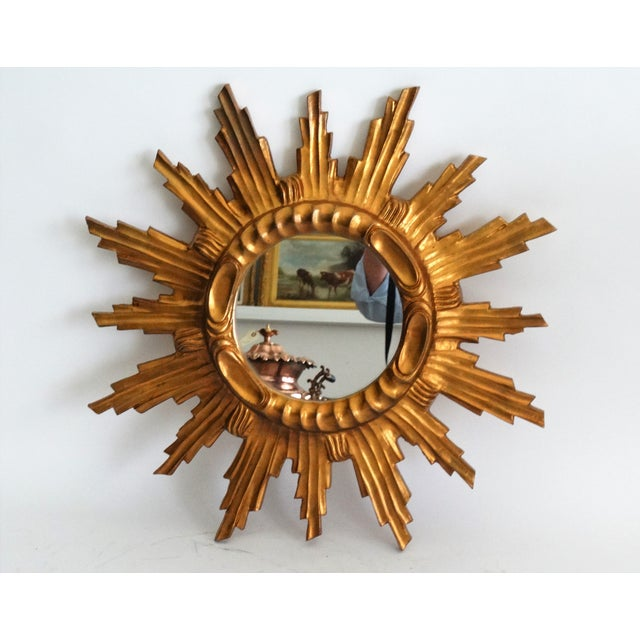 A large Mid Century French sunburst mirror. It is bright giltwood with lovely stepped rays, a raised center surround and...