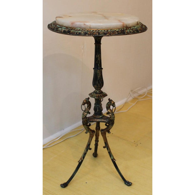 Elegant & sleek gryphon side table with an onyx top. The greenish tinge on the carved metal base and top add the perfect...