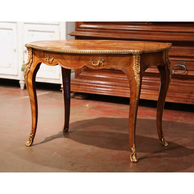 Decorate a study or office with this elegant antique table. Crafted in France, circa 1880, the center table stands on...