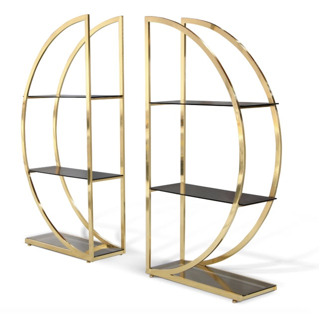 DECADENCE is a Bookcase with two ornate metal semi-circles joined in a glamourous union by sleek glass shelves and her...
