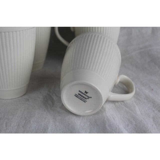 Six cream colored Wedgwood Windsor pattern mugs, made in England. Ribbed design with tapered cylindrical form. Microwave...