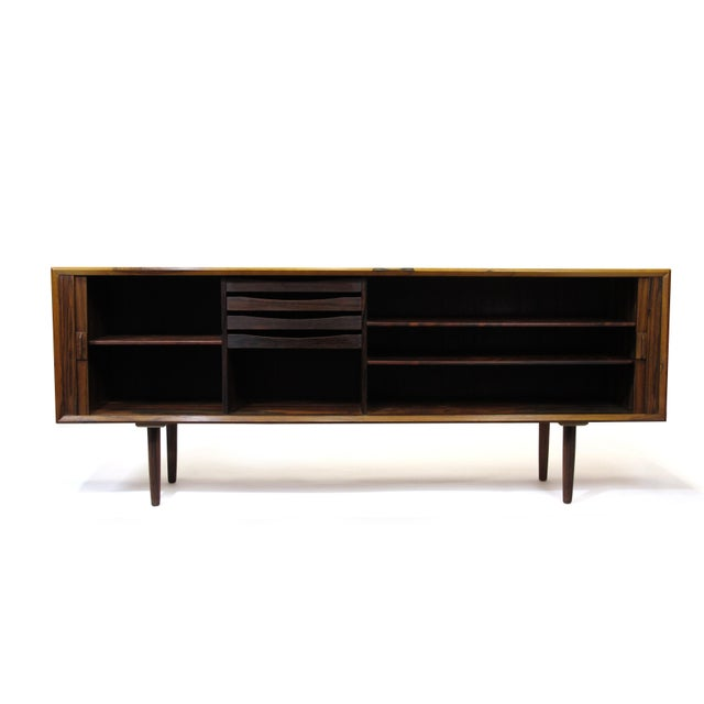 Rosewood credenza designed by Arne Vodder for Sibast, Denmark c. 1961. Features a book-matched tambour door front, which...