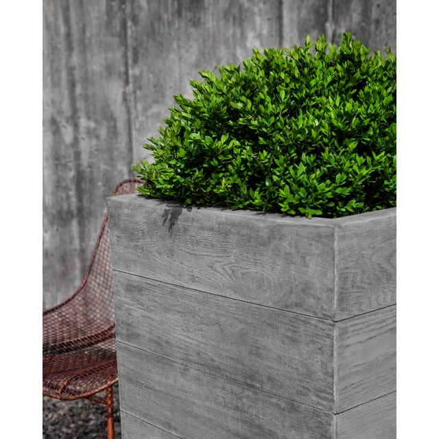 A cast stone planter with a woodgrain pattern in a Greystone finish. Available in multiple sizes, both square and...