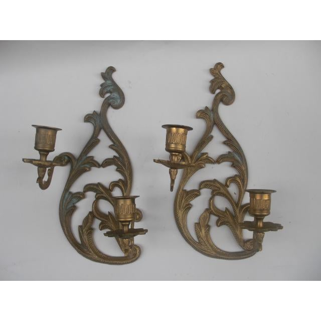 Pair of ornate cast brass leaf motif wall sconce candle holders, each holding a pair of candles. Some patina on brass.