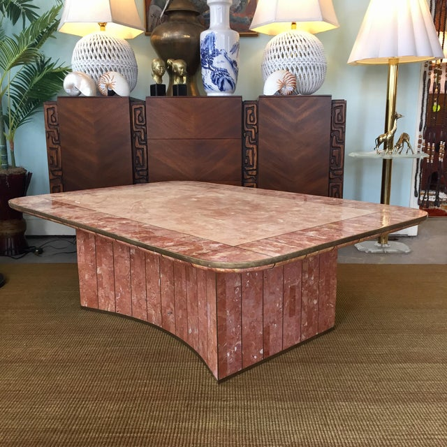 Beautiful coffee table by Casa Bique made of pink tessellated stone with a brass trim and inlay. Brass patina consistent...