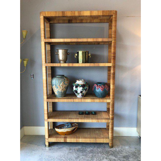Available for sale this fabulous Bielecky Brothers, woven rattan bookshelf. Great brass caps at the end of each legs add...