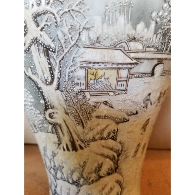 A vintage Chinese porcelain vase with a piped raised decoration over a hand painted snow scene. Soft muted shades. Makers...