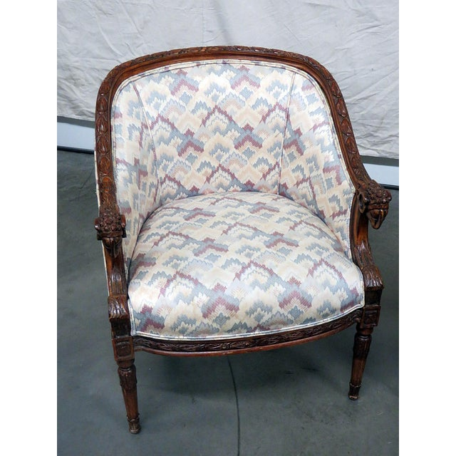 Pair of Regency style upholstered club chairs with carved rams heads.