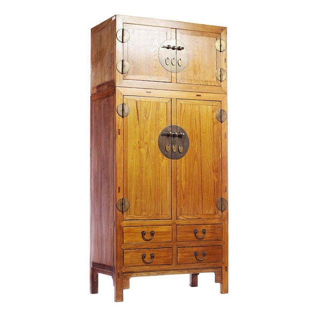 A Chinese elmwood compound cabinet with medallions from the 1800s. This Chinese 19th century large compound cabinet was...