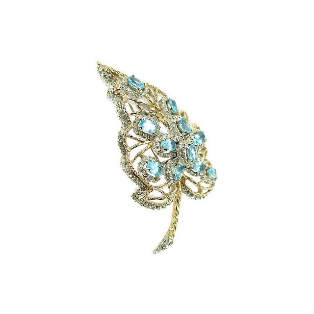 Offered here is a rhodium-plated crystal brooch from the 1940s. The three-dimensional motif depicts a domed leaf in an...