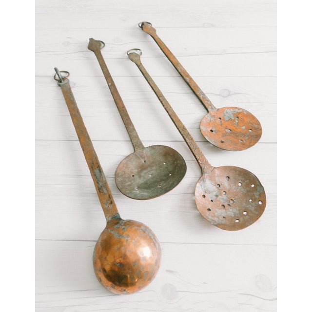Vintage hammered copper serving spoons with stamps and engravings on the long handles. They have hooks and rings to hang....