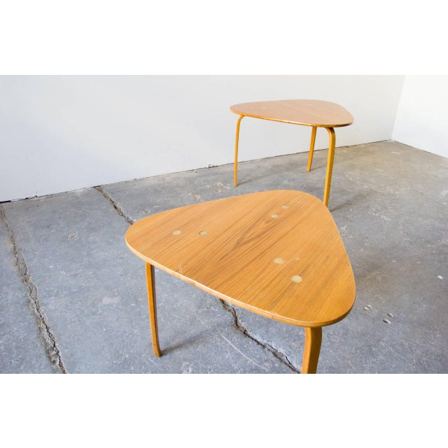 A pair of guitar pick tables by Yngve Ekström for DUX. The rounded triangle tops are accentuated by three multi-bent legs...