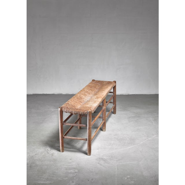 A Charlotte Perriand bench from circa 1960. The bench is made of wood, stands on six turned legs with stretchers and has a...