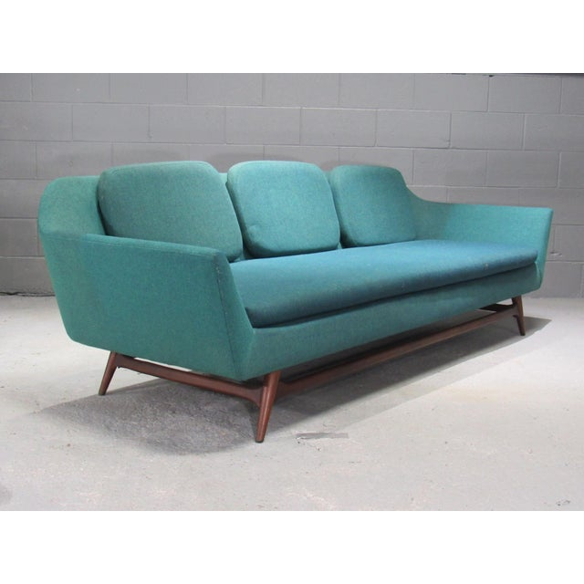This elegant sofa features a continuous seat cushion with three loose back cushions. The piece is from the 1950s.