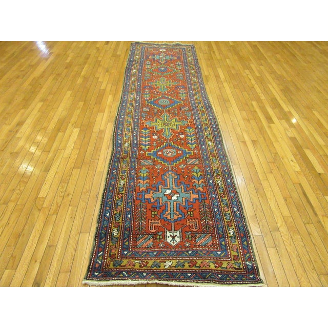 This is an antique hand knotted Persian Heriz runner rug . It is made with natural wool and dyes. The rug measures 3' 2''...
