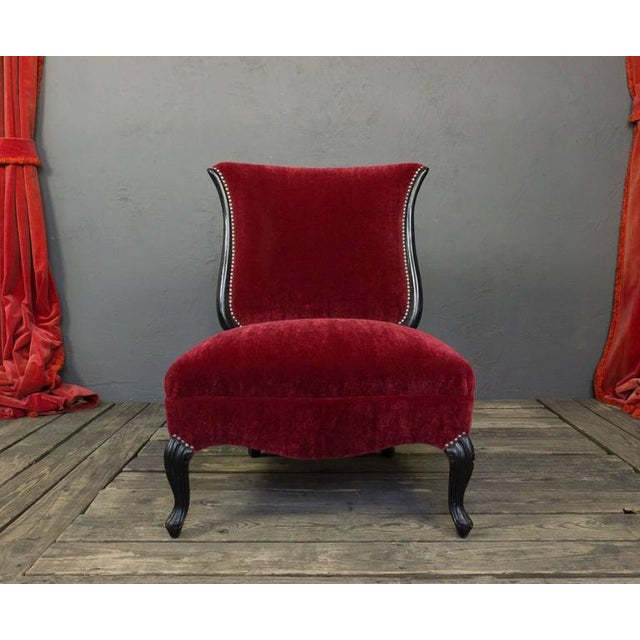 American 1950s slipper chair with recently ebonized legs and newly upholstered in red velvet and antique nickel nail heads.