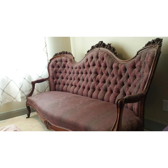 Beautifully ornate Victorian era sofa with floral carvings. Beautiful detail on arms and legs. On 4 original casters....