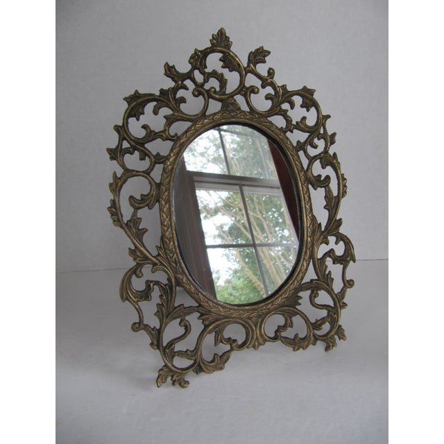 Ornate brass scroll vanity mirror. This classically designed piece would look beautiful gracing your vanity or bedside table.