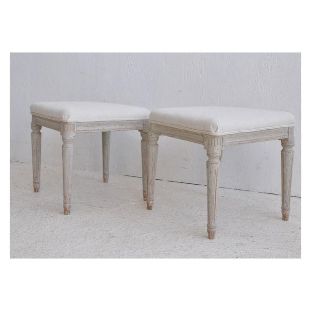 A pair of Swedish footstools from the Gustavian period, newly upholstered in linen and wearing a soft blue-gray paint.