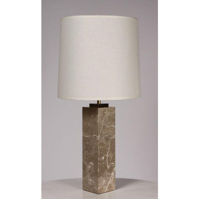An elegant column formed table lamp with a polished brass riser and fittings extending into a marble body with sumptuous...