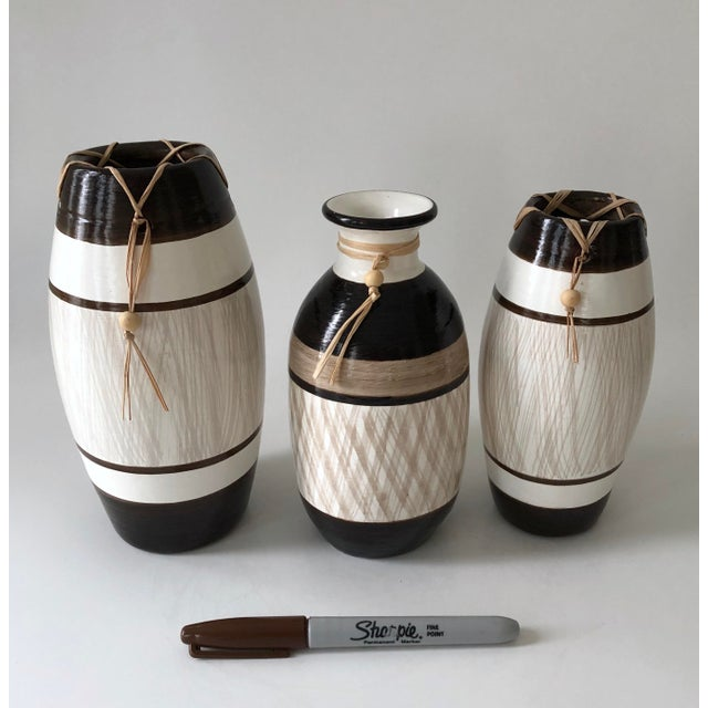 A grouping of three hand-made, authentic Brazilian pottery pieces with Raffia and bone bead detail. Label still on the...