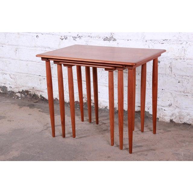 A gorgeous set of three Danish Modern teak nesting tables. The tables feature beautiful teak wood grain and sleek mid-...