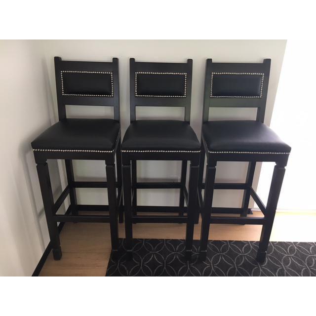 3 Dark Walnut bar stools, with black leather seat and back, and nickel nailheads. Originally handmade by Magart...
