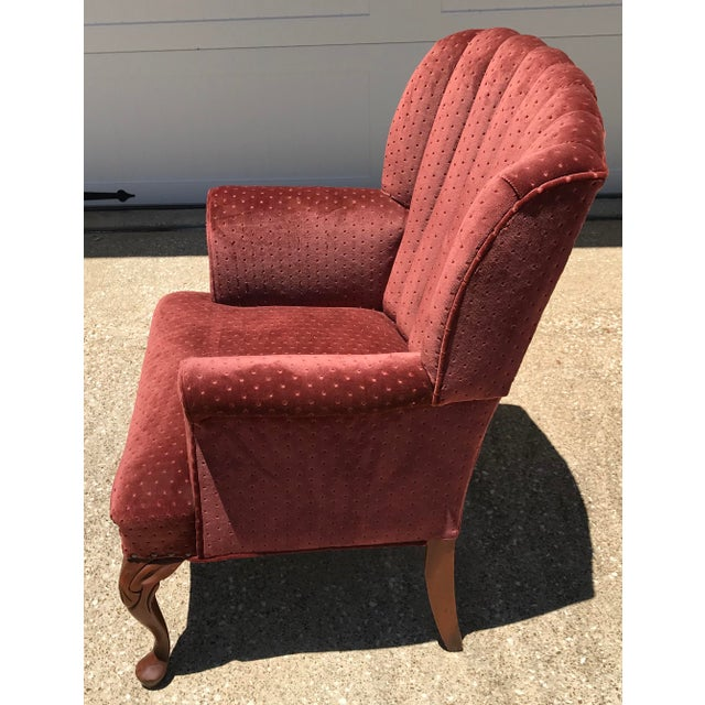 Nice velvet wingback chair! Almost a burnt orange but with a red tint.