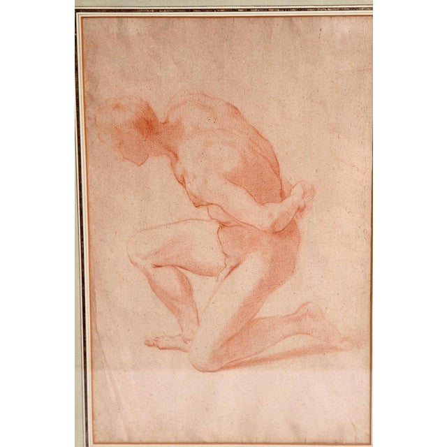 A realistically portrayed drawing of the male human figure kneeling with arms behind back. Modern matting and framed under...