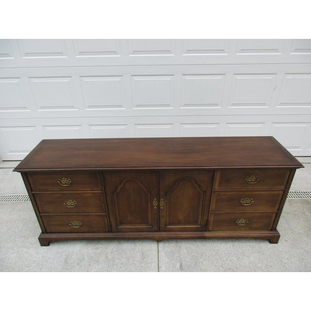 This Chippendale style nine drawer dresser is by Century Furniture and has banded drawers to each side of the center...